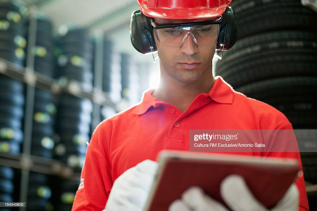 Worker with tablet computer in warehouse : Stock Photo