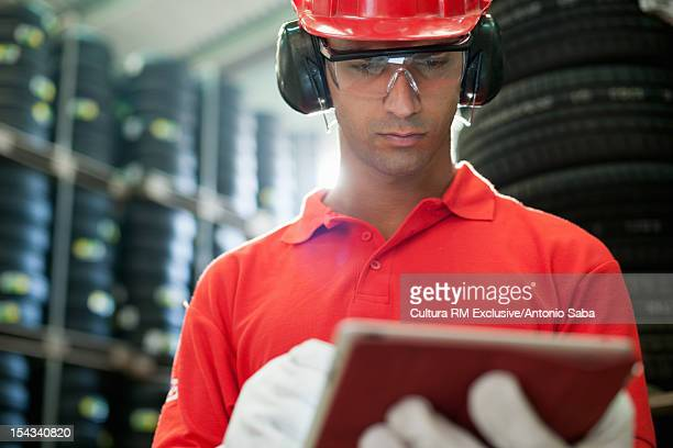 Worker with tablet computer in warehouse
