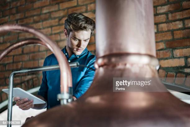 Worker with tablet PC examining vat in brewery
