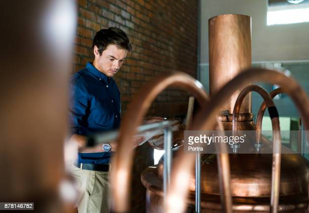 worker with tablet pc examining vat in brewery - distillery stock pictures, royalty-free photos & images