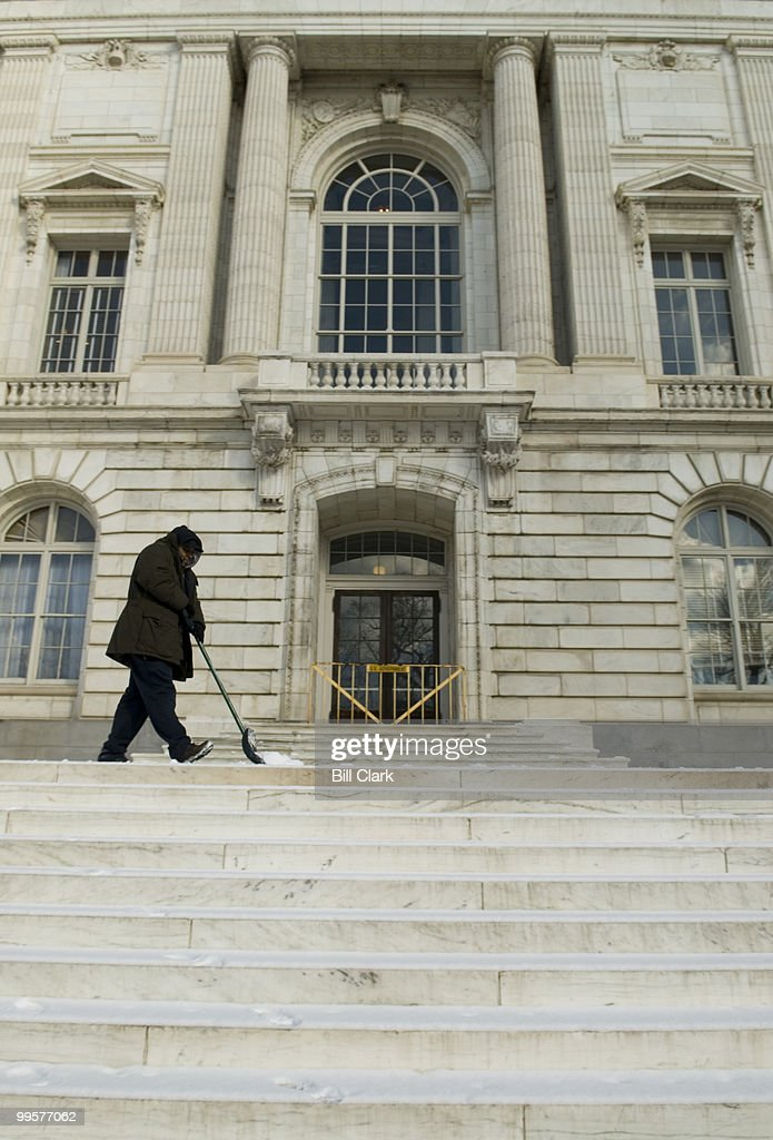 A worker with the Architect of the Capitol's office clears snow from the steps of the Russell Senate Office Building at the corner of Delaware Ave. and Constitution Ave. on Wednesday, Feb. 7, 2007.