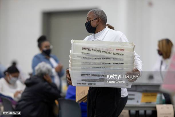 Worker with the Detroit Department of Elections carries empty boxes used to organize absentee ballots after nearing the end of the absentee ballot...