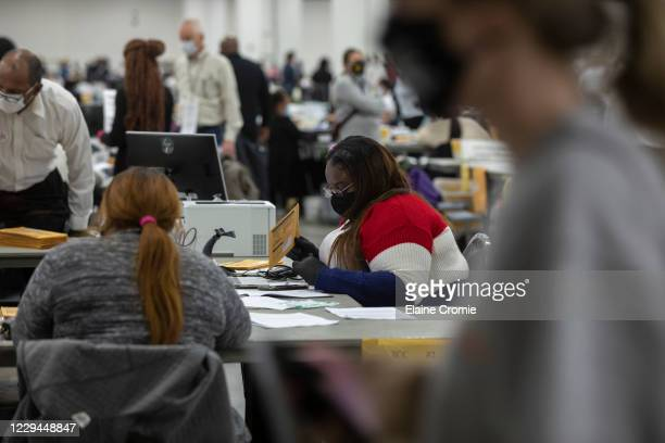 Worker with the Detroit Department of Elections helps process an absentee ballot at the Central Counting Board in the TCF Center on November 4, 2020...