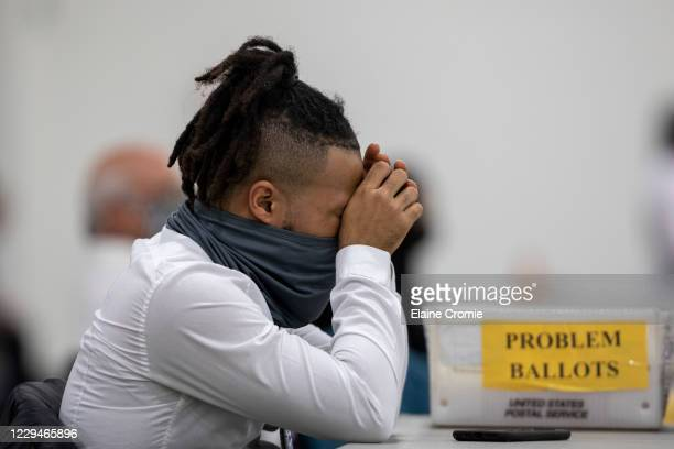 Worker with the Detroit Department of Elections takes a break after sorting through absentee ballots at the Central Counting Board in the TCF Center...