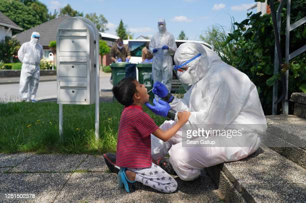 Worker with the German Red Cross dressed in full PPE takes a throat swab sample from local resident Arsalan in the village of St. Vit following a...