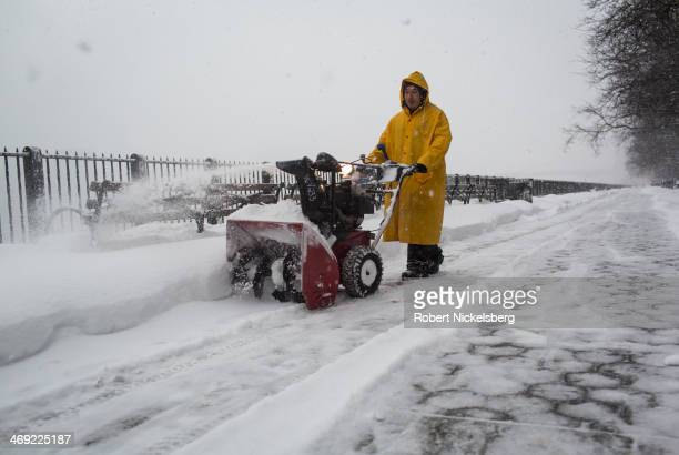 A worker with the New York City Parks and Recreation Department uses a snowblower along the Promenade during a snow storm February 13 2013 in the...