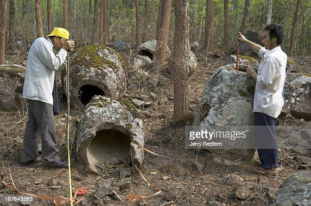 A worker with the UNESCO Preserving the Plain of Jars Project and a local villager mark a jar near Ban Phakeo village
