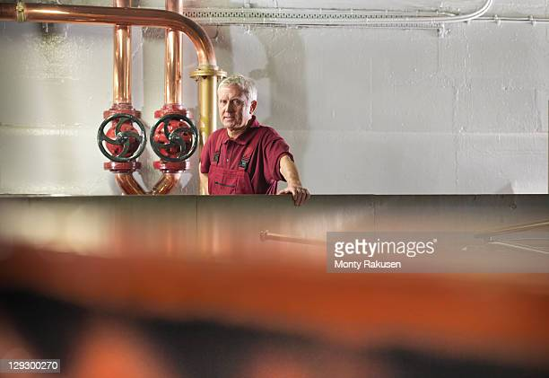 Worker with valves and whisky mash tun in distillery