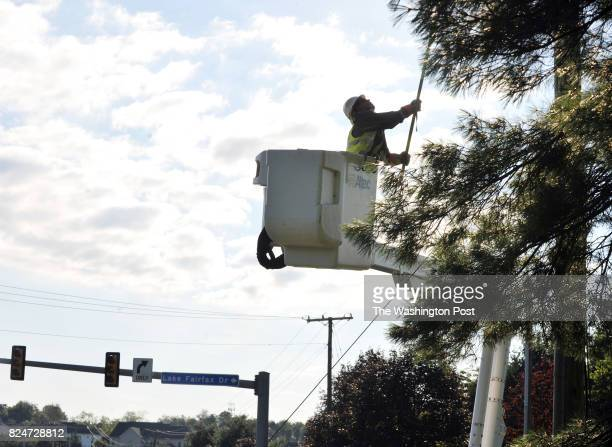 A worker with Virginia Dominion Power works to repair a power line at the corner of Baron Cameron Ave and Lake Fairfax Drive on July 26 in Reston VA...