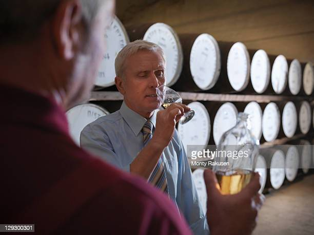 worker with whisky sample next to ageing whisky barrels in distillery - zakelijke kleding stock pictures, royalty-free photos & images