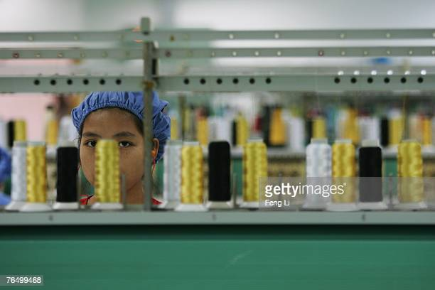 A worker work before the spinning machine at the production line of Dongguan Da Lang Wealthwise Plastic Factory on September 4 2007 in Dongguan of...