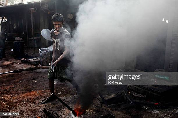 SADARGHAT DHAKA BANGLADESH A worker work in middle of the smoke at a ship propeller making factory in sadarghat dockyard Dhaka Bangladesg June 02...