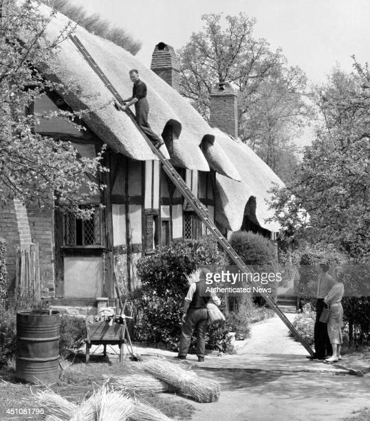 Worker work on Anne Hathaway's Cottage the wife of William Shakespeare in Shottery Warwickshire England Circa 1940