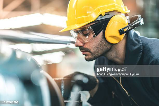 worker working in industry - ear protection stock pictures, royalty-free photos & images