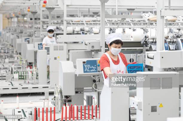 Worker works on a production line in a workshop of a textile company in Nantong, east China's Jiangsu Province, July 15, 2021. China's GDP grew 12.7...