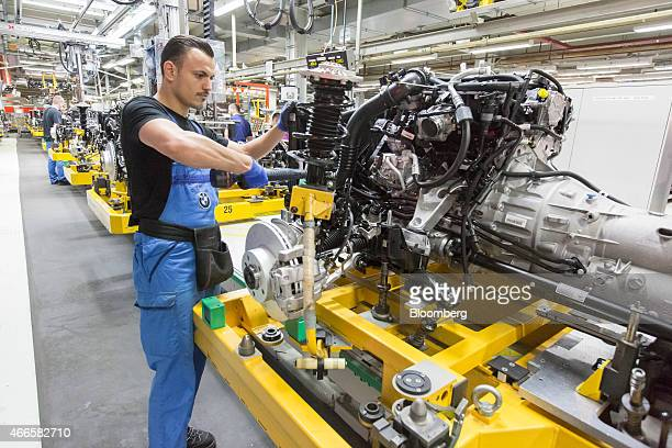 A worker works on the engine and drive train for a BMW 3 series automobile as it moves along the production line at the Bayerische Motoren Werke AG's...