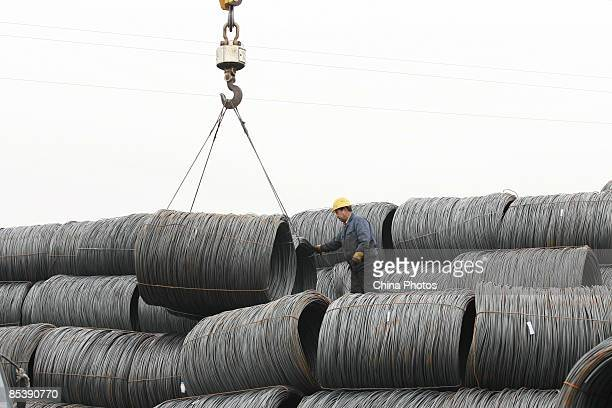 A worker works to load steel on a truck at a steel wholesale market on March 12 2009 in Shenyang of Liaoning Province China According to Li Yizhong...