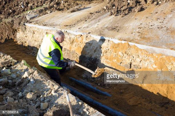 Worker works with shovel in a trench on pipeline construction site