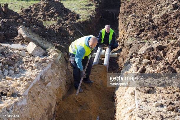 worker works with shovel in a trench on pipeline construction site - digging stock pictures, royalty-free photos & images