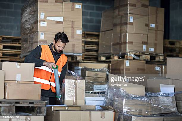 Worker wrapping cardboard boxes in the warehouse