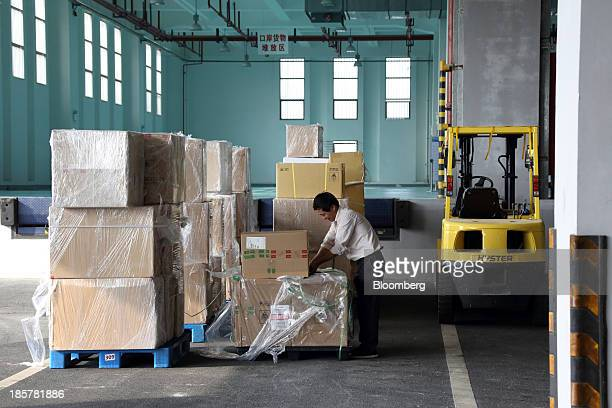 A worker wraps a box in front of a storage area in a logistics center at China Pilot Free Trade Zone's Pudong free trade zone in Shanghai China on...