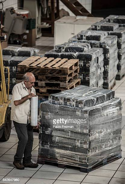 Worker wraps with plastic the packages of coffe that are going to be loaded into a truck to be delivered to supermarkets at Café Primavera Itapira...