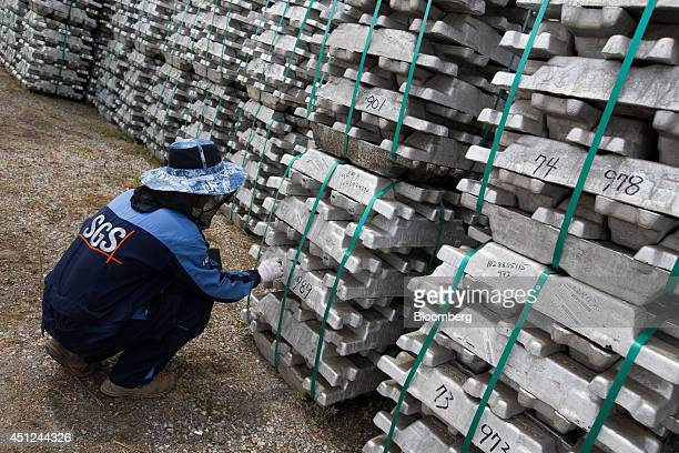 A worker writes the weight of a stack of aluminum ingots at the Public Procurement Service warehouse in Gunsan South Korea on Wednesday June 25 2014...