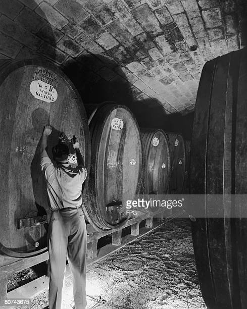 A worker writing on a cask in the cellar of the Inglenook Vineyard Company in Rutherford California 1941
