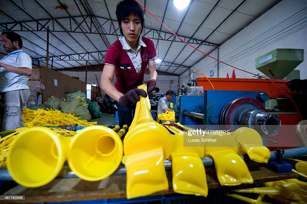 Worker Wu Dongjun takes newly-produced vuvuzelas out of the hot plastic mold, in Ninghai Jiying plastics factory June 28, 2010 in Xidian, near Ningbo, Zhejiang province, China. Almost 90 percent of the vuvuzelas used in the World Cup in South Africa are made in China. The Ninghai Jiying plastics factory is one of the vuvuzela Chinese manufactures. Its general manager Wu Yijun said 'from January to April this year, we were producing 250,000 vuvuzelas every day to fill containers that are exported'.