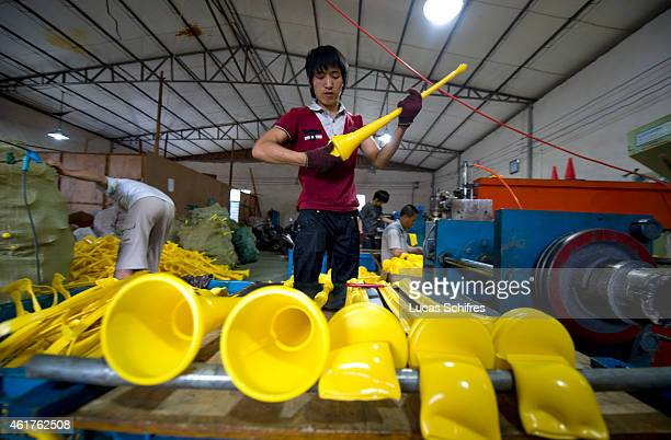 Worker Wu Dongjun takes newlyproduced vuvuzelas out of the hot plastic mold in Ninghai Jiying plastics factory June 28 2010 in Xidian near Ningbo...