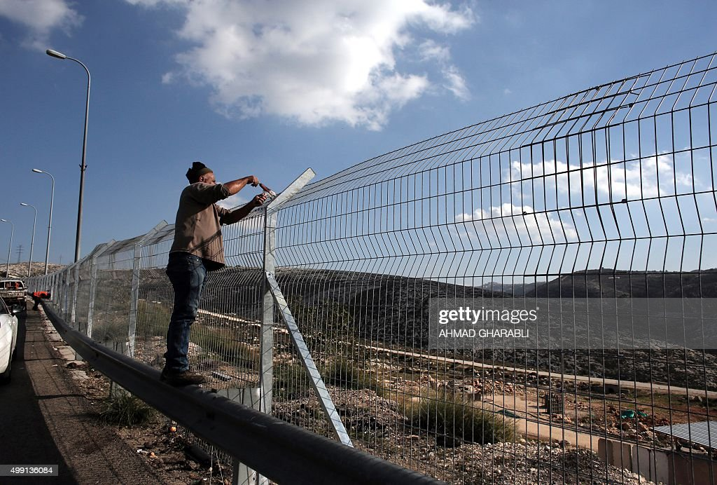 Workers add barbed wire to a security fence, part of Israel\'s ...