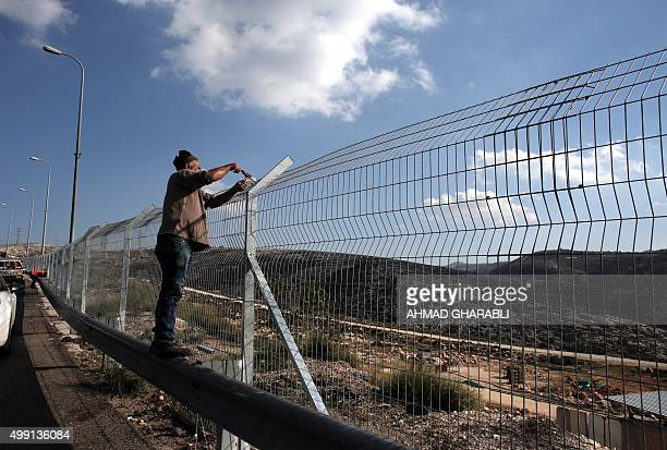 Workers add barbed wire to a security fence part of Israel's controversial separation barrier along highway 443 which runs from the outskirts of Tel...