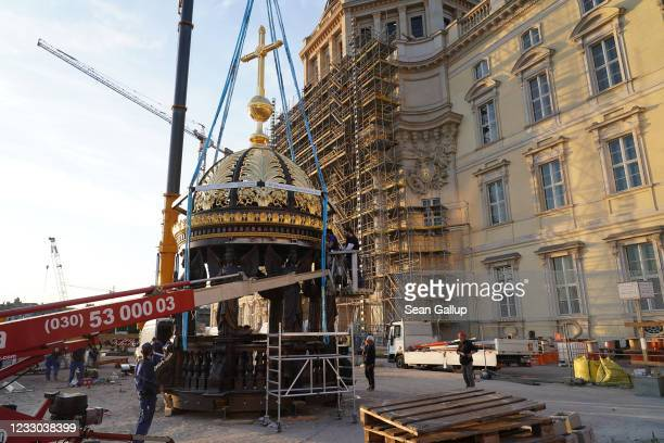 Workers add finishing touches to a supportive base of angels that had been joined to a gold-covered cupola and cross before a crane lifted the...