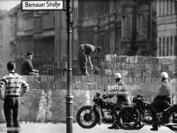 Workers add layers of brick to the Berlin Wall on Bernauer Strasse where critical incidents had occurred almost every evening The wall was also...