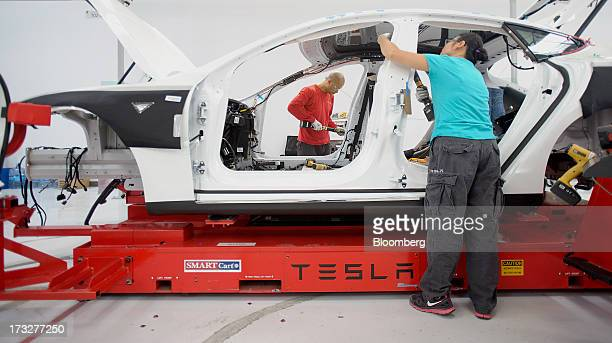 Workers add seat belts to a Telsa Motor Inc Model S sedan at the company's assembly plant in Fremont California US on Wednesday July 10 2013 Tesla is...