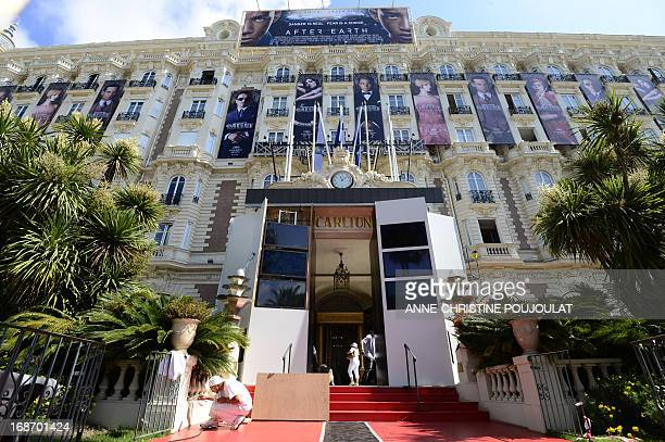 Workers add the finishing touch on May 14 2013 outside the Carlton Hotel in Cannes on the eve of the 66th edition of the Cannes Film Festival Cannes...