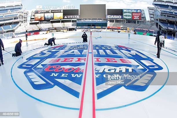 Workers add the lines and logos during the rink build for the 2014 Coors Light Stadium Series Games at Yankee Stadium on January 23 2014 in the Bronx...