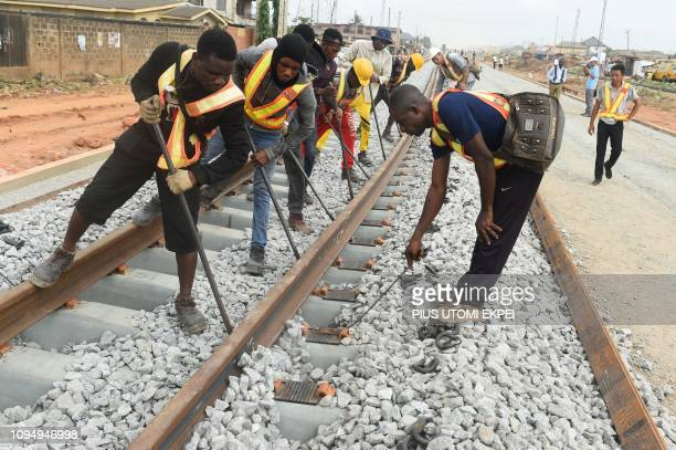 Workers adjusts the new standard gauge railway line under construction from Iju in Lagos to Abeokuta, Ogun State in southwest Nigeria, on February 7,...
