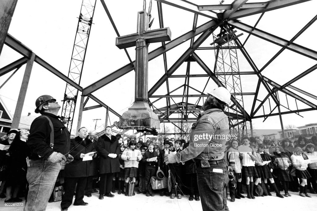 Workers and attendees looks on as the cross from the original St. William's Church, destroyed by a fire in September 1980, is raised for the topping-off ceremony of the new church building in the Dorchester neighborhood of Boston on March 4, 1983.