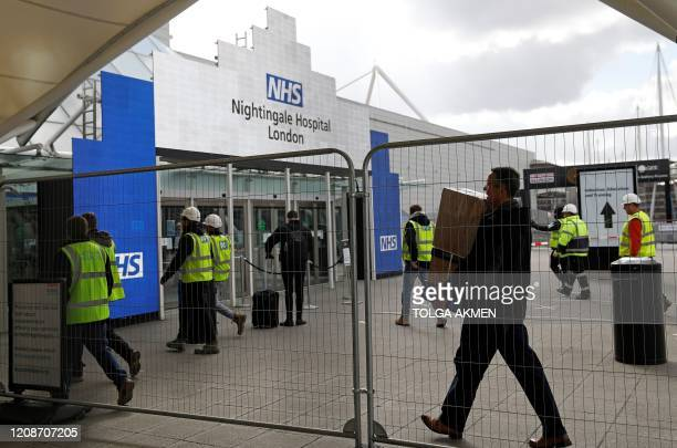 Workers and building contractors arrive at the ExCeL London exhibition centre in east London on March 31 where the NHS Nightingale field hospital has...