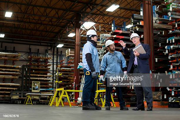 Workers and businessman in metal plant