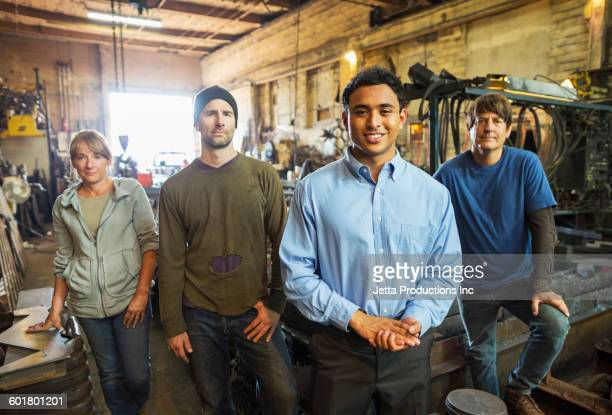 Workers and businessman standing in factory