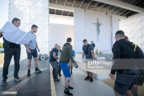 Workers and carpenters carry large block of refined wood for the table at the papal stage in preparation of the Apostolic Visit of Pope Francis on...