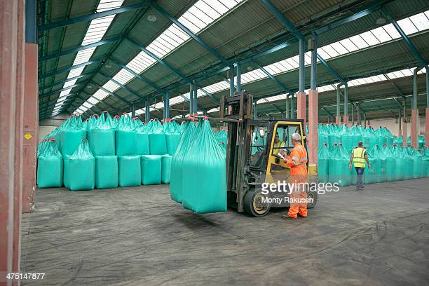 Workers and fork lift truck in bulk fertiliser store in port