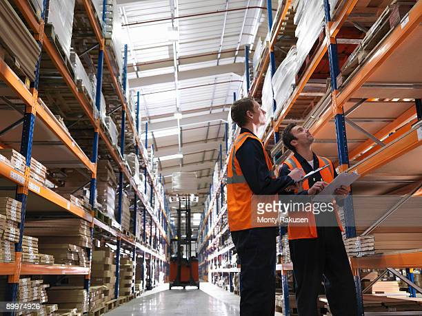 workers and forklift in warehouse - monty rakusen stock pictures, royalty-free photos & images
