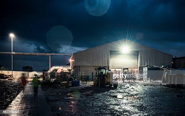 workers and machinery on industrial plant at night - dusk dark photos et images de collection