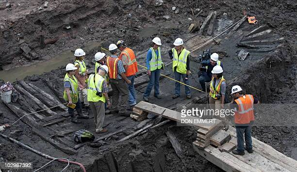 Workers and members of the media inspect the hull of a late 18th/early 19th century ship found at Ground Zer July 15 2010 in New York On the morning...