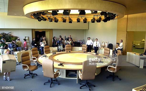 Workers and members of the media surround the meeting table 22 June 2002 at the G8 Summit site in Kananaskis Alberta Canada as preparations continue...