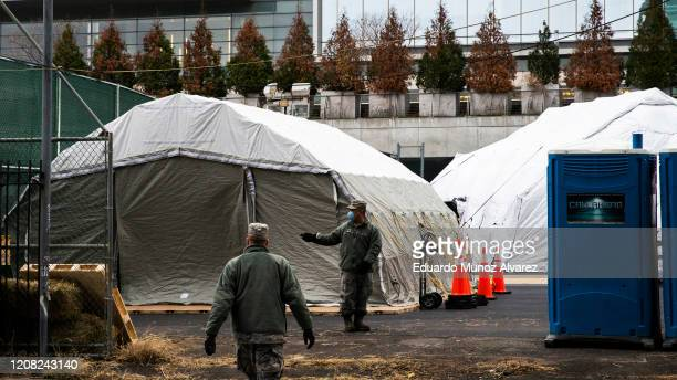 Workers and Military Members build a makeshift morgue outside of Bellevue Hospital on March 25, 2020 in New York City, New York. Across the country...