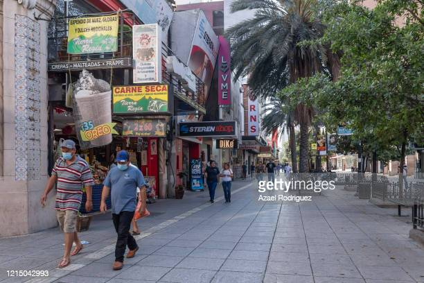 Workers and pedestrians still walk on the usually crowded Morelos Monterrey's main commercial pedestrian street on March 26 2020 in Monterrey Mexico...